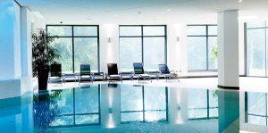 Das Bewegungsbad - Schwimmbad der Max Grundig Klinik mit Fensterfront und Liegestühlen