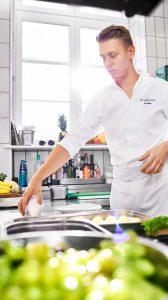 Junger Koch bei Essenszubereitung in Küche der Max Grundig Klinik