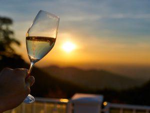 Abendstimmung und Sonnenuntergang mit Hand, das Weinglas hält