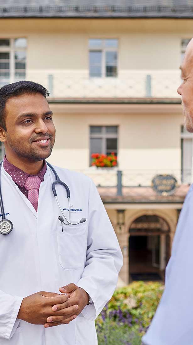 Arzt der Max Grundig Klinik im Gespräch mit einem Gast vor der Max Grundig Klinik