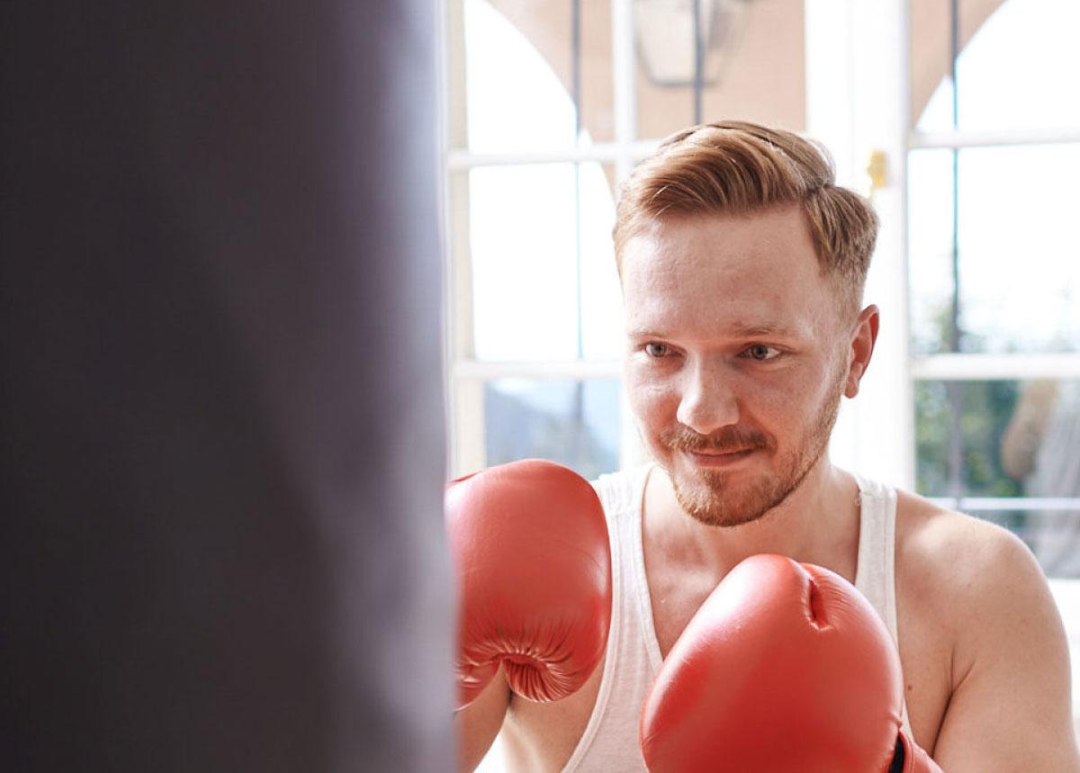 Boxer beim Training mit Sandsack und roten Handschuhen