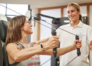 Frau bei Krafttraining mit Trainerin