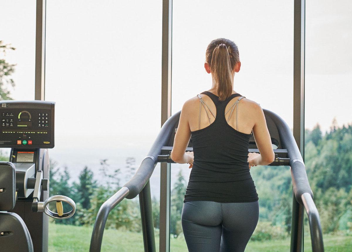 Frau trainiert auf Laufband, Rückansicht