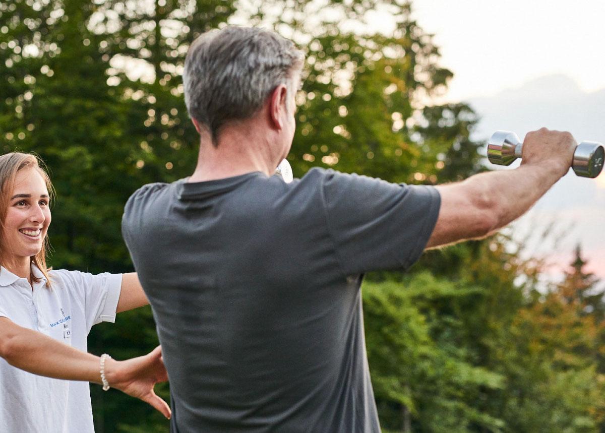 Mann mit Trainerin bei Hantel-Training im Freien