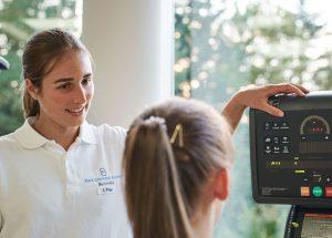 Frau bei Training auf Ergometer, Trainerin erklärt