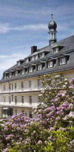 Parkanlage der Max Grundig Klinik mit blühenden Büschen und blauem Himmel