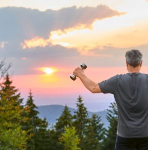 Mann beim Hanteltraining im Sonnenuntergang