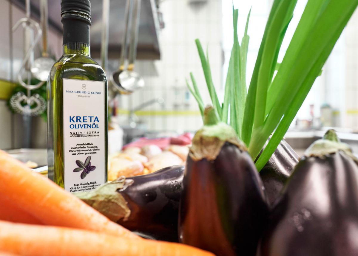 Flasche mit nativem Olivenöl und Gemüse im Hintergrund