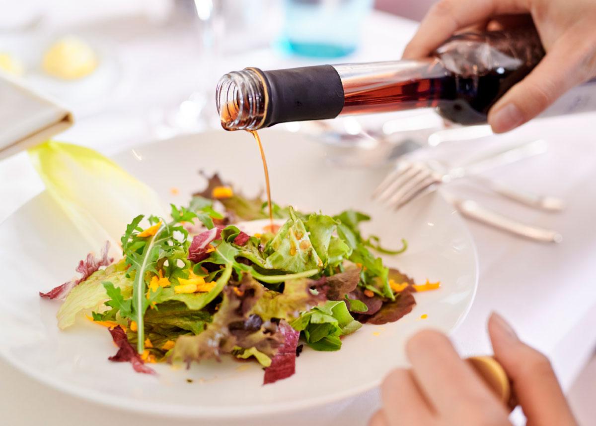 Teller mit buntem Salat und Flasche mit Essig