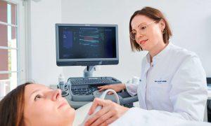 Frau Dr. Sonja Mayer mit Patient bei Ultraschalluntersuchung