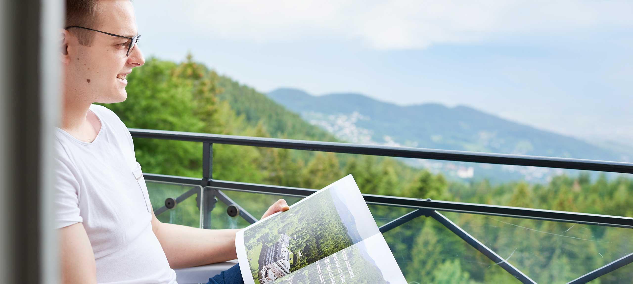 Mann genießt die Aussicht mit dem MAX Magazin