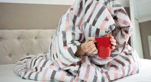 Frau trinkt Tee unter einer Bettdecke