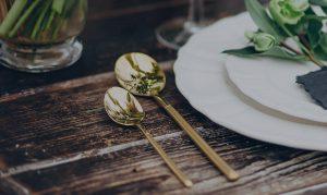 Goldenes Besteck neben Teller