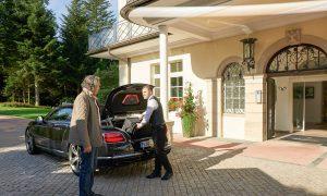 An- oder Abreise eines Gastes in der Max Grundig Klinik, Darstellung Serviceleistung am Auto mit Gast und Mitarbeiter, der Koffer einlädt