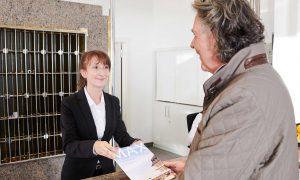 Gast im Gespräch mit Service-Personal der Max Grundig Klinik, nimmt MAX-Magazin in Empfang