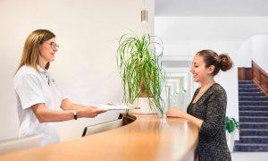 Gast im Gespräch mit Service-Personal der Max Grundig Klinik an der Rezeption