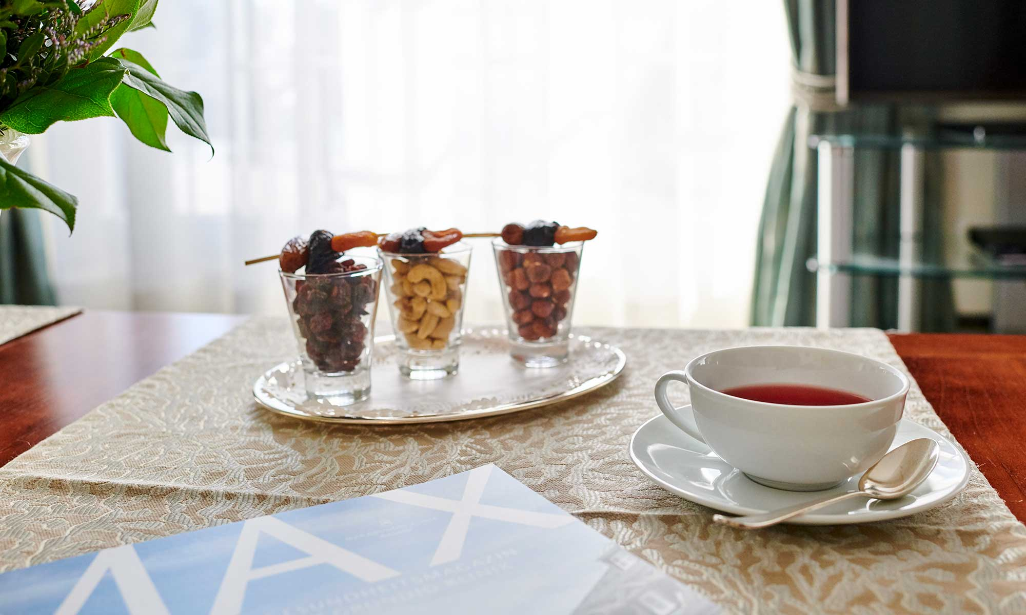 Teetasse mit kleinen Schlemmereien und das MAX-Magazin